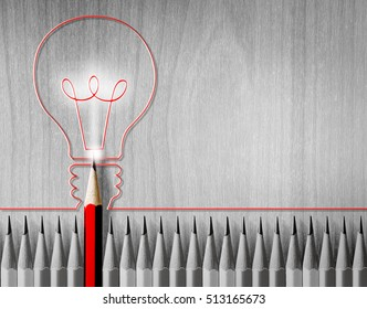 Red pencil drawing light bulb in the middle of the black and white pencil. The concept of energy