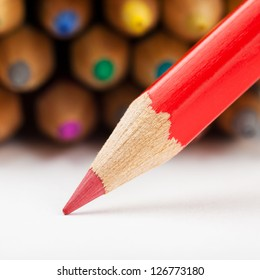 red pencil draws or writing on white paper sheet, colored pencils as background