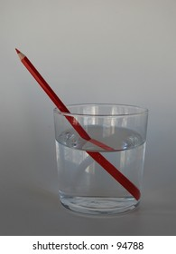 Red pencil in a glass of water, depicting refraction, illusion.