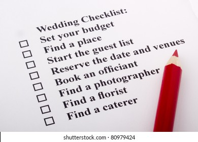 Red pencil laying on a wedding checklist.
