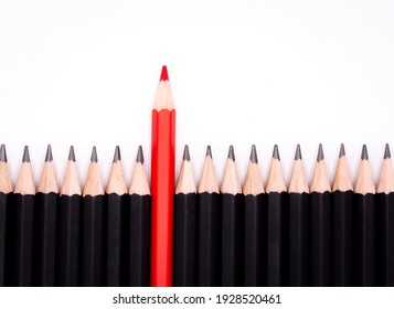 Red pencil in the middle role of black pencil out from crowd of plenty identical black fellows to show leadership, independence, strategy, think different concept.