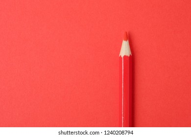 Red pencil on red paper background. Close up.