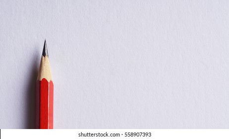 Red pencil on white paper background - copy space concept