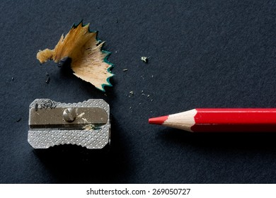 Red pencil and sharpener on black background