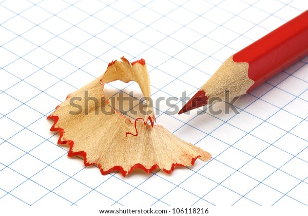 Red pencil shavings on a piece of paper