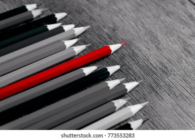 Red pencil stand out from the rest of the pencils in black and white.Focus at red color pencil.
