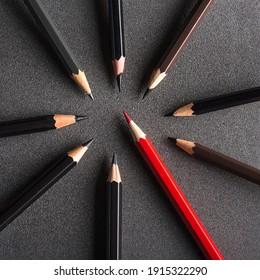 Ein roter Bleistift, der zwischen den dunklen Bleistiften steht