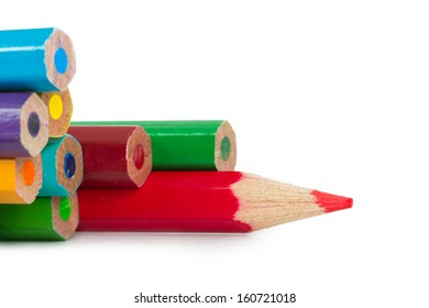 Red pencil standing out from colorful pencils, isolated on white background.