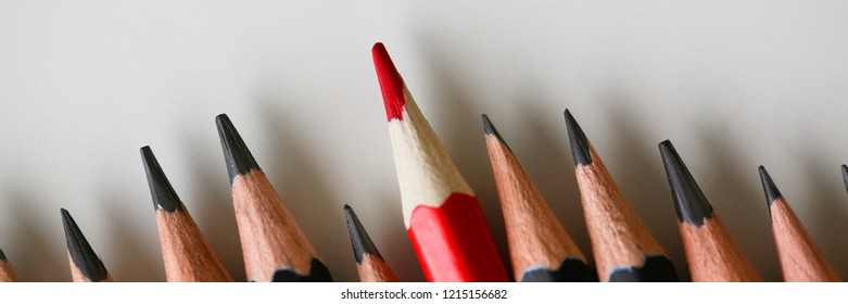 Red pencil standing out from crowd of plenty identical black fellows. Leadership uniqueness independence initiative strategy dissent think different teamwork business success concept