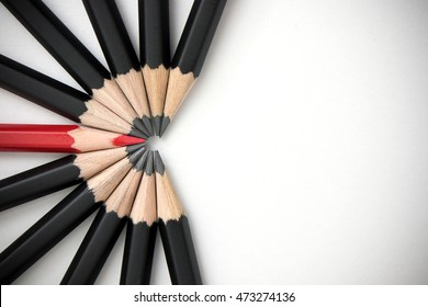 Red pencil standing out from crowd of plenty identical black fellows. Leadership, uniqueness, independence, initiative, strategy, dissent, think different, teamwork business success concept.