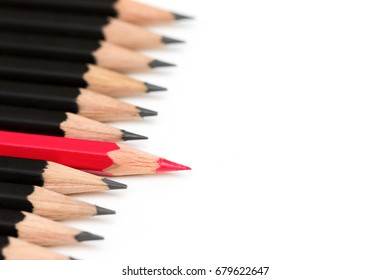 Red pencil standing out from crowd of plenty identical black fellows on white table. Leadership, uniqueness, independence, initiative, strategy, dissent, think different, business success concept.
