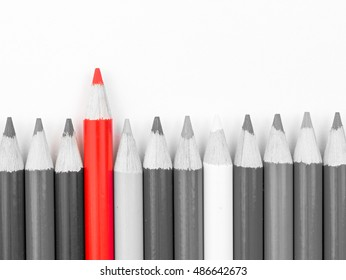 Red pencil standing out from monochrome pencils crowd, copy space available. Stand out from the crowd concept