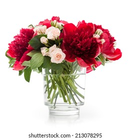 Red peonies and pink miniatures roses bunch in a vase isolated on white.