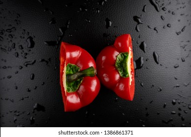 Red pepper on a black background. Bulgarian pepper on a black background with water drops. Bulgarian pepper is cut in half.Bulgarian pepper on a black background in water drops. Red sweet
