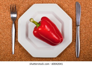 A red pepper on a white plate with knife and fork on a cork placemat