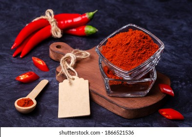 Red pepper powder in a bowl on a dark stone background. Selective focus.