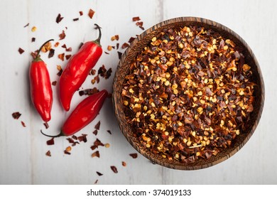 Red Peppers with crushed pepper flakes in a bowl with scattered flakes on the table focus on the flakes in the bowl