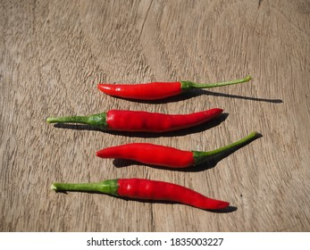 Red peppers on the wooden table - Shutterstock ID 1835003227