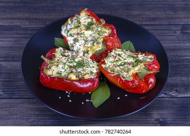 Red peppers stuffed with cream cheese with herbs and garlic, baked in grill in black plate, close up