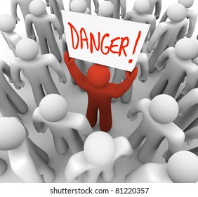 A red person stands out in a crowd holding a sign that reads Danger to warn and alert other people to a risk, hazard or other dangerous condition