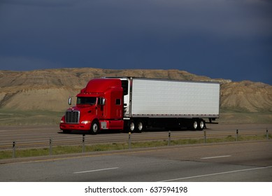 A Red Peterbilt Tractor Pulls a White Trailer. All Markings Removed. May 7th, 2017 Rock Springs, Wyoming, USA