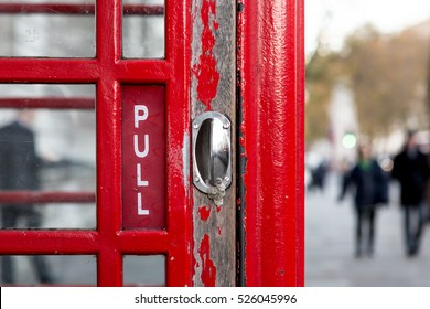 Red Phone Booth Door Handle Closeup in London, England, with Walking People in the Background