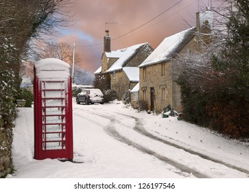 Red phone box and cottages in snow, Cotswolds, England