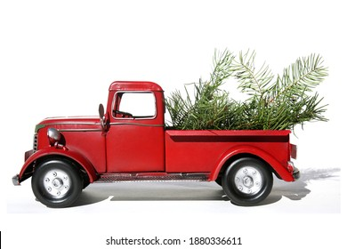 Red Pick Up Truck. Vintage Pick Up Truck with Christmas Tree Branches in back. Isolated on white. Room for text. Pine Tree Branches in a red pick up truck. Merry Christmas. Happy Holidays.