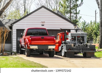 Red pickup truck and older red truck with welder on the back parked in the driveway in front of a residential garage and house