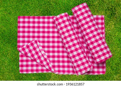 Red picnic blanket. Red checkered picnic cloth on blurred sun-flooded lush grass with focus on napkin. Beautiful backdrop for your product placement or montage.