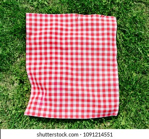 Red picnic cloth on grass top view.
