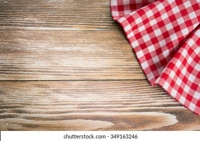 Red picnic cloth on wooden background.Napkin tablecloth on old wood with empty space for text.