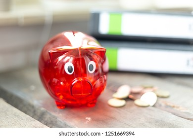 Red piggy Bank with money and folder on a table