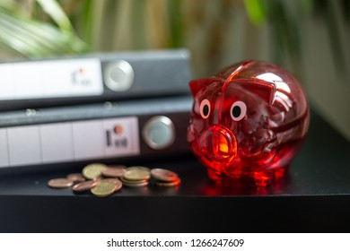 Red piggy bank with some change on the desk
