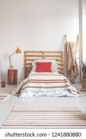 Red pillow on single bed with striped bedding in spacious bedroom interior, real photo with copy space on the empty wall