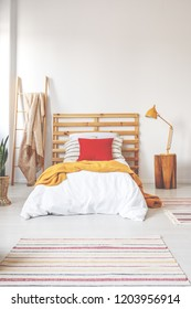 Red pillow and orange blanket on comfortable teenager bed with white bedding in elegant oldschool bedroom interior with copy space on the white wall
