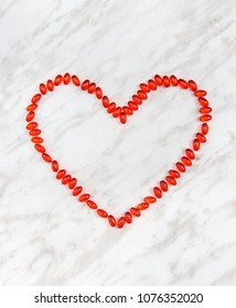 Red pills heart on marble background. Healthcare concept. Frame with copy space.