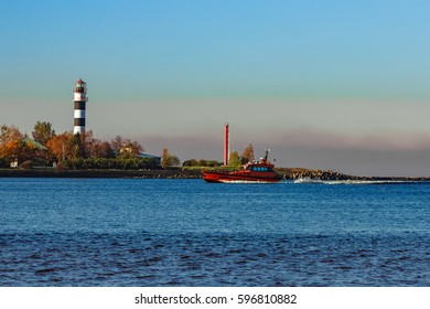 Red pilot ship moving past the lighthouse in Riga