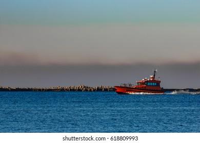 Red pilot ship moving past the breakwater dam in Riga, Europe