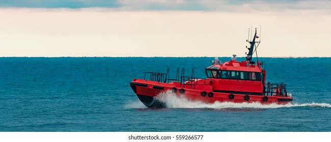 Red pilot ship moving at speed from Baltic sea
