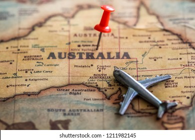 Red pin and mini airplane on Australia part of world map. Travel to Australia concept. Selective focus.