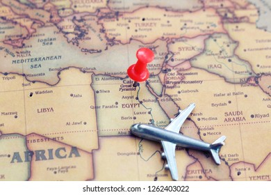 Red pin and mini plane on Egypt part of world map. Flights to Egypt concept. Selective focus.