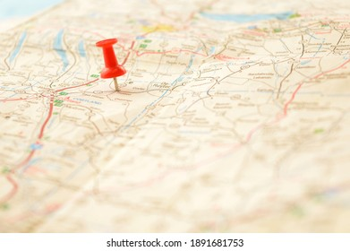 A red pin pressed into a map detailing a point of interest.