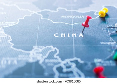 Red pin to the world map at China, blur map and selective focus of red pin.