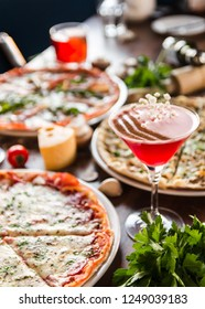 Red, pink cocktail in a martini glass, several pizzas, garlic, tomato, alcohol, copy space, top viev, Served table full of food, appetizers