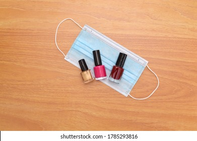 Red, Pink Gold Nail Polish on face masks wood grain background