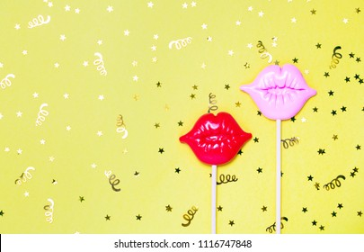 Red and pink lips for fun on yellow festive background with golden confetti. Bright celebration concept. Top view, flat lay. Copy space for text.