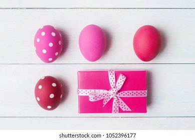 Red and pink painted Easter eggs and gift box over light wooden background.