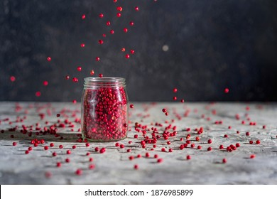 Red or pink peppercorns falling in a glass jar on grey textured table,  black background. Motion spices image. Copy space.