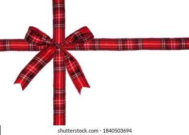 Red plaid Christmas gift bow and ribbon arranged as wrapped gift box isolated on a white background